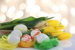 Wielkanoc pstrzył jajka w nasadkach i kolorów żółtych tulipanach Fotografia Stock