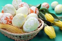 Wielkanoc pstrzył jajka i tulipany w koszu Zdjęcia Stock
