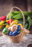 Wielkanoc Ręcznie robiony malujący Easter jajka w kosza i wiosny tulipanach Obraz Royalty Free