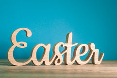 Wielkanoc - rzeźbiący drewniany tekst przy błękitnym tłem świąteczna dekoracja pojęcie Easter szczęśliwy Fotografia Stock