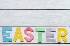 Wielkanoc składał papierowego origami kolorowego literowanie na białym drewnianym deska wieśniaka tle Obrazy Stock