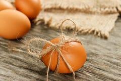 Wielkanoc Surowi jajka w łęku na parciaku na drewnianym stole Zdjęcia Royalty Free