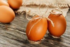 Wielkanoc Surowi jajka w łęku na parciaku na drewnianym stole Obraz Stock
