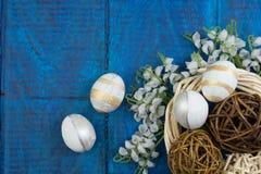 wielkanoc szczęśliwy Jajka na drewnianym stołowym tle Piłki, wianek wyplatający od winogradów Odbitkowa przestrzeń dla teksta wie Fotografia Stock