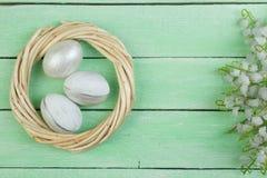 wielkanoc szczęśliwy jajka odizolowywający na drewnianym stołowym tle Piłki, wianek wyplatający od winogradów Odbitkowa przestrze Obraz Royalty Free