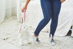 wielkanoc szczęśliwy Piękna seksowna młoda kobieta jest ubranym królików ucho na butach i trzyma śliczną królik zabawkę Zdjęcia Royalty Free
