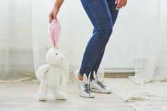 wielkanoc szczęśliwy Piękna seksowna młoda kobieta jest ubranym królików ucho na butach i trzyma śliczną królik zabawkę Zdjęcia Stock