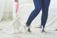 wielkanoc szczęśliwy Piękna seksowna młoda kobieta jest ubranym królików ucho na butach i trzyma śliczną królik zabawkę Fotografia Royalty Free