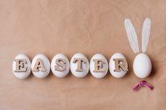 Wielkanoc, tła rzemiosła papier, biali jajka słowo wielkanoc jajko w postaci królika Zdjęcie Royalty Free