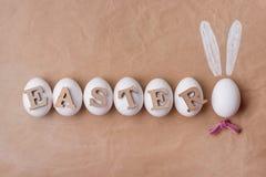 Wielkanoc tła rzemiosła papier, biali jajka słowo wielkanoc jajko w postaci królika Zdjęcia Stock