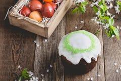 Wielkanoc tort i malujący jajka, wiosna skład na drewnianym stole Zdjęcia Stock
