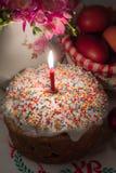 Wielkanoc tort z zaświecającą świeczką na uroczystym stole Obrazy Stock