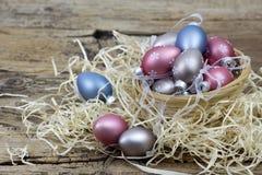 Wielkanocna dekoracja - kolorowi malujący jajka w koszu obraz stock