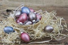Wielkanocna dekoracja - kolorowi malujący jajka w koszu fotografia royalty free