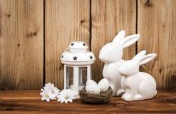 Wielkanocna dekoracja - króliki z Easter jajkami w gniazdeczku na drewnianym tle Obrazy Stock