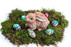 Wielkanocna dekoracja: Malujący królik na mech i jajka Zdjęcie Royalty Free