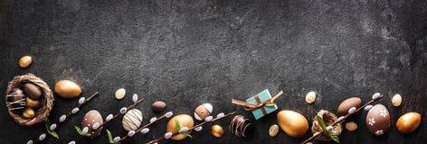 Wielkanocna dekoracja Złoci jajka na Ciemnym iłołupka tle Fotografia Stock