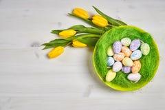 Wielkanocna dekoracja z jajkami i tulipanami na białym stole Fotografia Stock