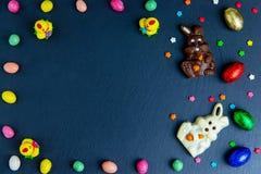 Wielkanocna kartka z pozdrowieniami z kolorow? cukierek ram?, czekoladowymi jajkami i cukierkami, Odg?rny widok na kamienia stole zdjęcia stock