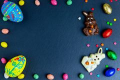 Wielkanocna kartka z pozdrowieniami z kolorowym cukierku jajkiem, czekoladowym kr?likiem i jajkami ramowym i Wielkanocnym, fotografia stock
