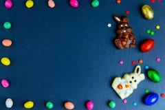 Wielkanocna kartka z pozdrowieniami z kolorowym cukierku jajkiem, czekoladowym kr?likiem i jajkami ramowym i Wielkanocnym, zdjęcie royalty free