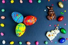 Wielkanocna kartka z pozdrowieniami z kolorowym cukierku jajkiem, czekoladowym kr?likiem i jajkami ramowym i Wielkanocnym, fotografia royalty free