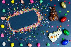 Wielkanocna kartka z pozdrowieniami z kolorowym cukierku jajkiem, czekoladowym kr?likiem i jajkami ramowym i Wielkanocnym, zdjęcia royalty free