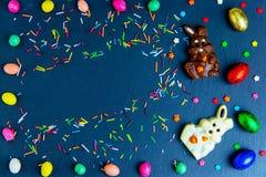 Wielkanocna kartka z pozdrowieniami z kolorowym cukierku jajkiem, czekoladowym kr?likiem i jajkami ramowym i Wielkanocnym, zdjęcia stock
