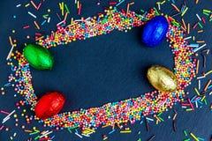 Wielkanocna kartka z pozdrowieniami z kolorowym cukierku jajkiem, czekoladowym kr?likiem i jajkami ramowym i Wielkanocnym, zdjęcie stock