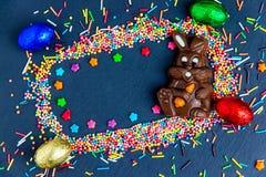 Wielkanocna kartka z pozdrowieniami z kolorowym cukierku jajkiem, czekoladowym kr?likiem i jajkami ramowym i Wielkanocnym, obrazy stock