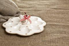Wielkanocne ceramiczne jajeczne filiżanki na tekstylnym tle Zdjęcia Stock
