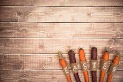Wielkanocne marchewki na drewnianym tle w wieśniaku projektują Zdjęcie Stock