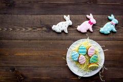 Wielkanocnego królika i Easter jajek ciastka Wielkanocni symbole i tradycje Ciemna drewniana tło odgórnego widoku kopii przestrze Zdjęcie Royalty Free