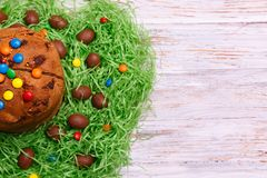 Wielkanocnego Paska tortowi i czekoladowi jajka w zielonej trawie na drewnianym tle, odgórny widok obraz royalty free