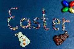 Wielkanocnego pojęcia stubarwni cukierki rozkładają w postaci wielkanocy na zmroku - błękitny tło z czekoladowym królikiem fotografia stock
