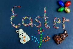 Wielkanocnego pojęcia stubarwni cukierki rozkładają w postaci wielkanocy na zmroku - błękitny tło z czekoladowym królikiem zdjęcia stock