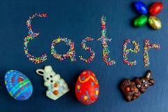 Wielkanocnego pojęcia stubarwni cukierki rozkładają w postaci wielkanocy na zmroku - błękitny tło z czekoladowym królikiem zdjęcia royalty free