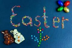 Wielkanocnego pojęcia stubarwni cukierki rozkładają w postaci wielkanocy na zmroku - błękitny tło z czekoladowym królikiem zdjęcie stock