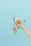 Wielkanocnej dekoraci drewniana łyżka z barwionymi cukrowymi składnikami dalej Fotografia Stock