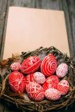 Wielkanocni czerwoni jajka z ludowego bielu wzoru inside ptakiem gniazdują na prześcieradle papier na nieociosanym drewnianym tle Obrazy Royalty Free