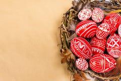 Wielkanocni czerwoni jajka z ludowego bielu wzoru inside ptakiem gniazdują na prześcieradle papieru tło Odgórny widok Ukraińscy t Obrazy Royalty Free