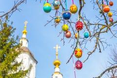 Wielkanocni drzewni jajka z kościół w tle Zdjęcia Royalty Free