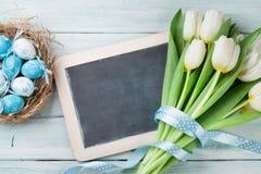 Wielkanocni jajka, chalkboard i biali tulipany, Fotografia Stock