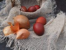 Wielkanocni jajka i cebulkowe plewy w koszu fotografia royalty free