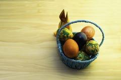Wielkanocni jajka kłama w błękitnym koszu i papierowym króliku na żółtym drewnianym stole, pasta fotografia royalty free