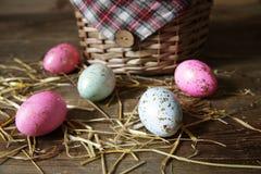 Wielkanocni jajka na łozinowego kosza tle na drewnianym wieśniaka stole zdjęcie stock