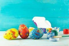 Wielkanocni jajka na błękitnym drewnianym tle z barwioną czerwoną błękitnej zieleni żółtą farbą z muśnięciem obraz royalty free