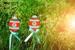 Wielkanocni jajka na drewnianych kijach i zielonej trawie Zdjęcia Royalty Free