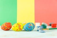 Wielkanocni jajka na multicolor drewnianym tle z farbami i muśnięciem zdjęcie royalty free