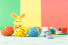 Wielkanocni jajka na multicolor drewnianym tle z farbami, muśnięciem i Wielkanocnym królikiem, zdjęcia stock